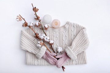 Warm clothes, cotton flowers and burning candles on white background