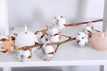 Cotton flowers and burning candles on shelf
