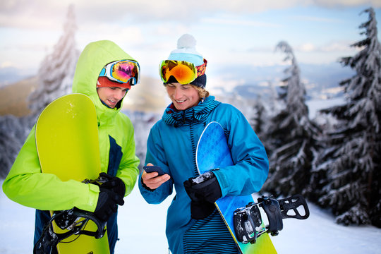 Two snowboarders talking and holding smartphones. Friends looking at cellphone and communicating in social network sharing their photos in app with internet connection wearing colorful fashion outfit.