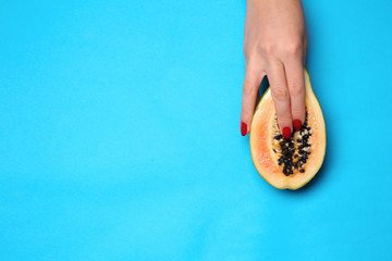 Female hand and half of fresh papaya on color background. Erotic concept