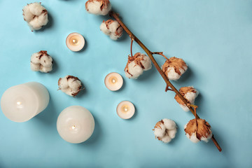 Flat lay composition with burning candles and cotton flowers on color background