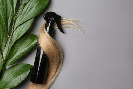 Spray bottle with cosmetic for hair on grey background, top view