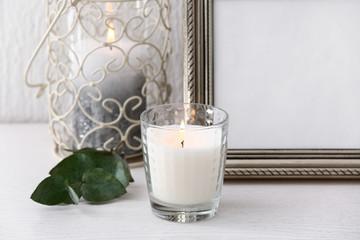 Burning candle near photo frame on table