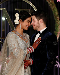 Bollywood actress Priyanka Chopra and her husband singer Nick Jonas pose during a photo opportunity at their wedding reception in New Delhi