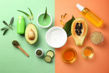 Flat lay composition with fruits and natural cosmetics on color background