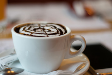 white cup with cappuccino, latte, coffee, mobile phone on a wooden table. wallpaper
