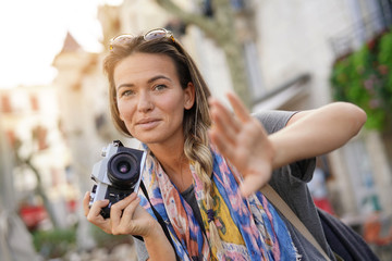 Attractive young woman taking photographs with an SLR
