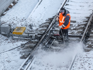 the railway worker cleans a railway track