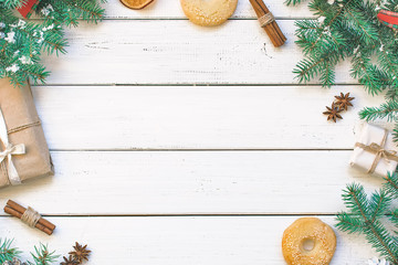 Christmas gift, pine cones, fir branches, spruce, cookies, lights, oranges, cinnamon, snowflakes and festive tinsel on the white light natural wooden surface old desk texture background, wood planks g