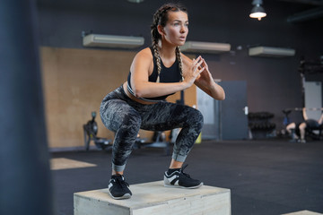 Woman in a gym doing squats Wall mural
