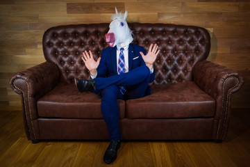 Funny unicorn in elegant suit siting on sofa like a boss and showing do not bother me gesture. Portrait of unusual man at home. Freaky guy in mask.