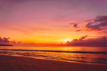 Waves in ocean and warm bright sunset in Bali. Ocean with sunset colors