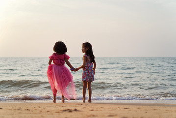 Two Asian kid girls holding hands each other on the beach while they are playing together. Seen from their back in the evening sunset. Vacation and holiday on beach concept.