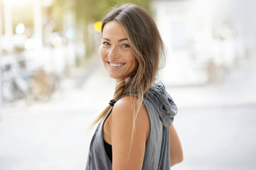 Woman in urbanwear turning around and smiling at the camera