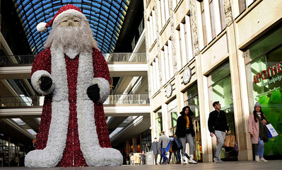 People carry shopping bags as they walk past a figure of Santa Claus outside a shopping mall in Berlin