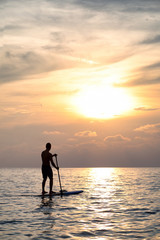 Sunset Silhouette Of Young Handsome Man Paddling On Surfboard Toward The Horizon In The Open Sea Beautiful Scenic Sunset