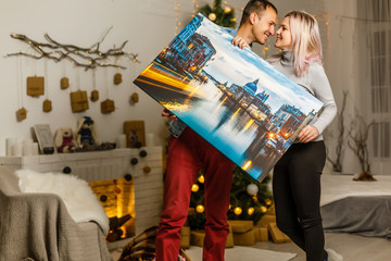 Fototapeta Happy young woman canvas and her boyfriend holding while moving into new home