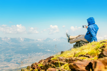 woman hiker taking photo with her smart phone on the top of the mountain peak