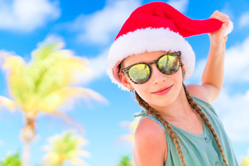 Portrait of little girl in Santa hat during Christmas beach vacation
