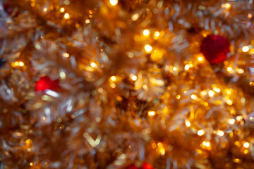 Abstract. Blurred. Season Greeting. Golden and Red Merry Christmas background. Sparkling ball ornaments on a gold and sparkle Christmas tree for a Happy New Year festive decoration and celebration.