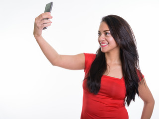 Studio shot of happy beautiful woman smiling while taking selfie