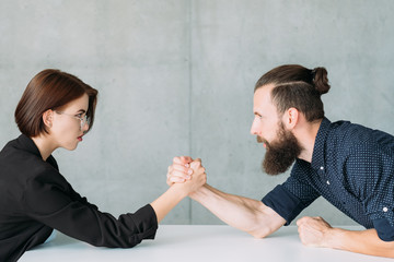 business man and woman arm wrestling at table. competition rivalry and fighting.