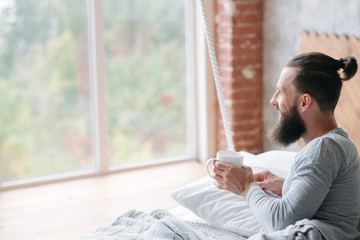 man having cup of coffee lying in cozy bed looking out the window. morning leisure