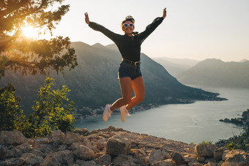 woman jumping on the top of hill. kotor with sunset on background