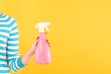 woman holding pink spray bottle on yellow background. home cleaning