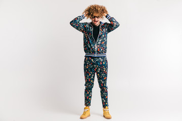Adult shylish man in fashion clothes, yellow sneakers posing on white studio background. Excited bizarre crazy shocked male shouting, tearing hair. Surprised funny happy young brazilian guy screaming.