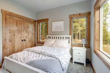 Small yet cozy bedroom interior features white bed with headboard