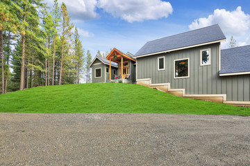 New gray wooden country house exterior with green grass.