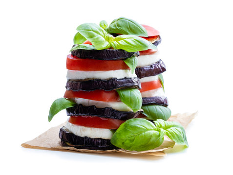Stack of grilled eggplant with tomato and mozzarella isolated on white