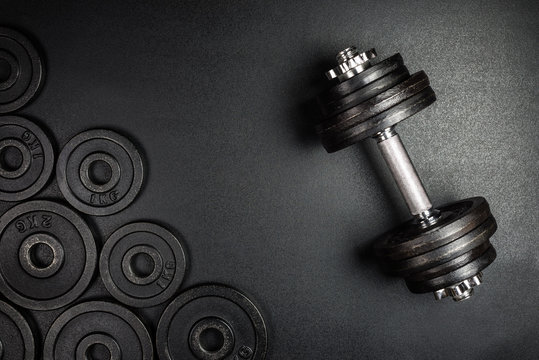 Gym dumbbells with black metal weights 1kg and 2kg on black background with copy sapce, Photograph taken from above