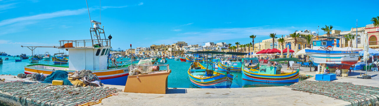 MARSAXLOKK, MALTA - JUNE 18, 2018: Walk the shipyard with a view on scenic wooden luzzu boats, fishing vessels and old village edifices, stretching along the coast, on June 18 in Marsaxlokk