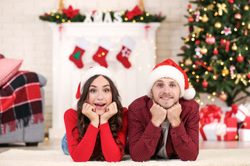 Young couple in santa hats lying at home near christmas tree