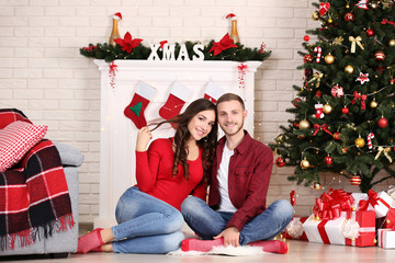 Happy young couple sitting at home near christmas tree