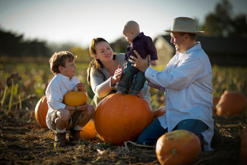 Happy family having fun together in a pumpkin patch.