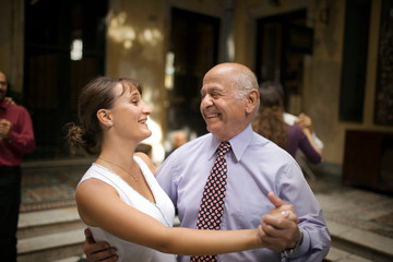 View of an elderly man dancing with a woman.