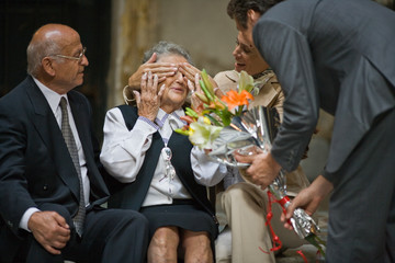 Mid-adult woman covering her senior mother's eyes as her brother presents a bouquet of flowers while sitting near her senior father.