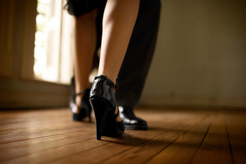 Cropped view of the legs of a couple on a dance floor.