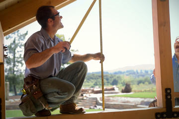 Male builder holding a tape measure on a house under construction.