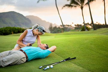 Smiling female golfer sits on the green and leans over a smiling male golfer lying on the ground next to her with his arm around her.