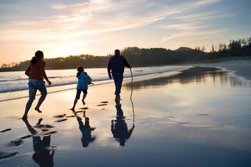 people run along the beach at sunset