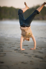 Young girl doing a handstand on the beach.