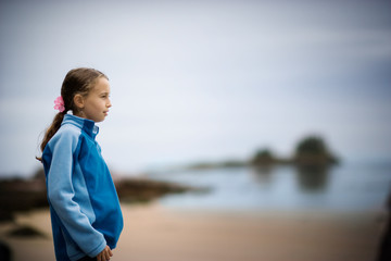 Young girl standing on a beach.