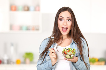 Beautiful woman eating fresh salad in the kitchen