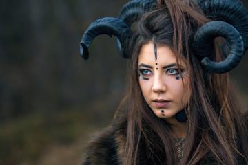 Outdoor portrait of beautiful scandinavian viking woman warrior with blue eyes wearing ram horns. Female hunter with specific makeup wearing fur collar