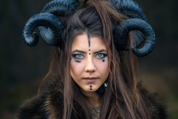 Outdoor portrait of beautiful scandinavian viking woman warrior with blue eyes wearing ram horns looking at camera. Female hunter with specific makeup wearing fur collar