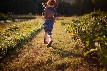 Young girl running between plants in a garden.